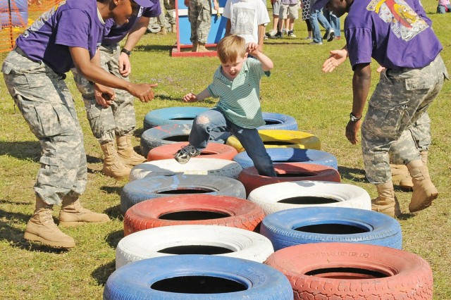 Cooper Griffin, 5, races to step through tires at the Warrant Office Career College's obstacle course as warrant officer candidates cheer him on at Fort Rucker's SpringFest. Because SpringFest was so close to St. Patrick's Day, an Irish theme was chosen for the first-of-its-kind festival. Photo by Marti Gatlin