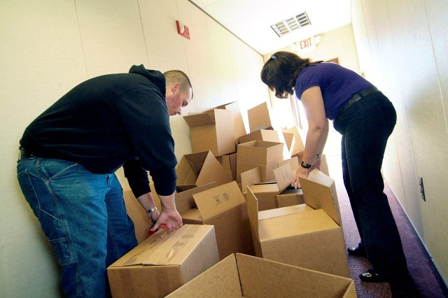 Justin Erosh, an Army Reserve Soldier with the 430th Military Police Detachment, and Ida Gonzalez prepare boxes to be sent as care packages to troops deployed overseas during the Hearts Apart Program sponsored by Army Community Service here. Erosh's best freind died in 2008 while serving in Iraq.