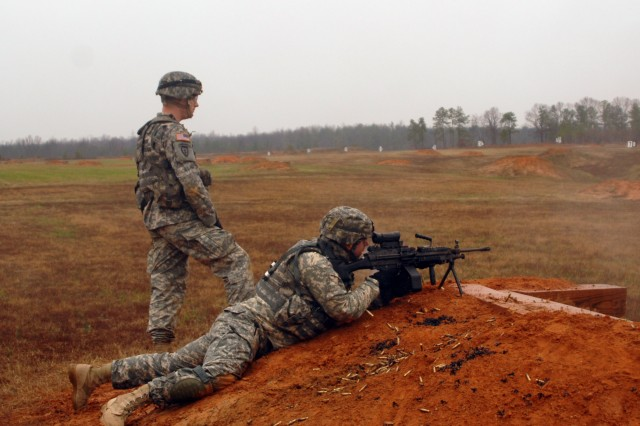 Sgt. 1st Class Theodore Tremblay, platoon sergeant for 2nd Platoon, Company A, aims and shoots as Staff Sgt. David Butler looks on.  Conditions of cold weather, rain and mud did not deter the Soldiers of Company A as they worked on the basics of infantry tactics for three days at Fort A.P. Hill, Va.
