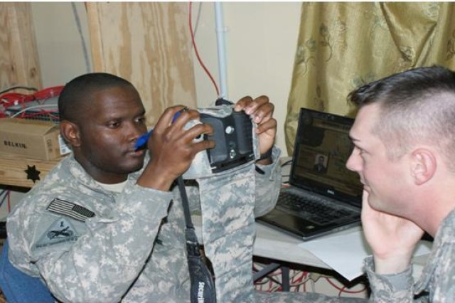 Staff Sgt. Orrin Thompson, a senior intelligence analyst, gives a block of instruction on the Army's Biometrics Automated Toolset System to Spc. Jonathan Friar.