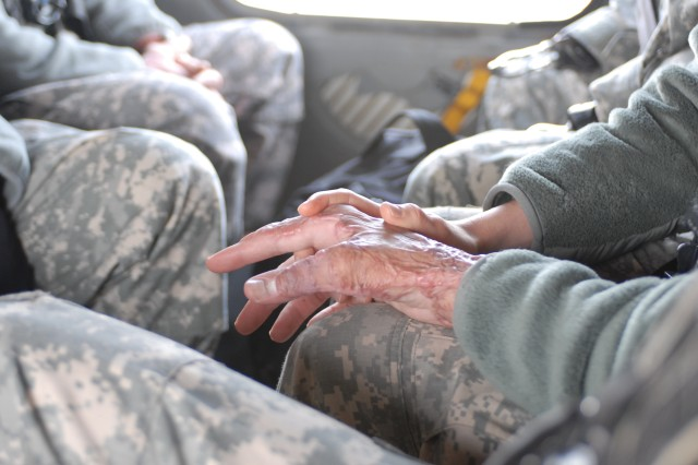 Capt. Sam Brown rests his hand on the knee of his wife, Capt. Amy Brown, during a flight to Camp Korean Village, near the Syrian and Jordanian borders Dec. 29. Brown was hit by an improvised explosive device in Kandahar, Afghanistan, in 2008, and suffered third degree burns to 30 percent of his body.