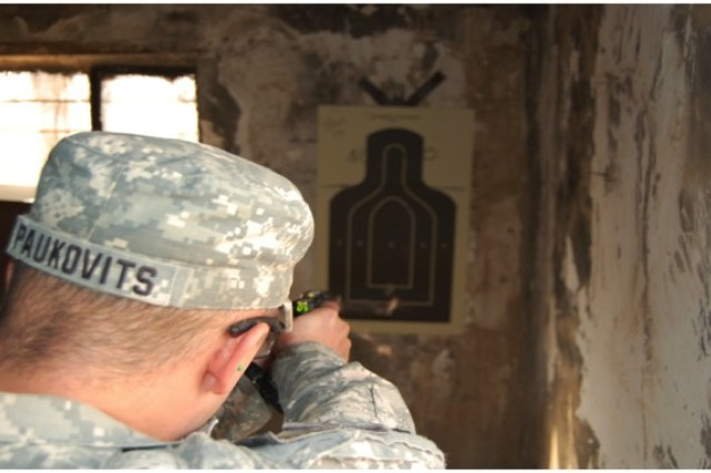 """SSG John Paukovits, 2nd PLT C Company,  takes aim at a silhouette target with a taser gun as his PLT attends a day long certification course for various types of non-lethal weapons."""""""