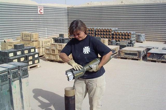 During her deployment as a QASAS employee with the Army Materiel Command, Angela Bailey inspected several different types of munitions. Here she inspects 120mm HE mortar rounds from a forward operating base. The rounds were missing the propellant support assembly. Bailey and other employees at the ammunition supply point replaced the assemblies prior to storage or shipment.