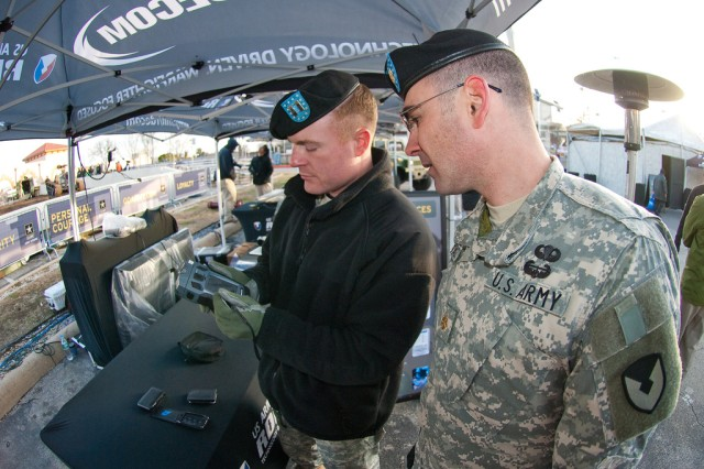"The Army Research Laboratory's Capt. Scott Shaffer (left) shows Maj. Mike Baker the ""Phraselator,"" a hand-held language translation device during a technology demonstration in San Antonio, Texas, Jan. 7."