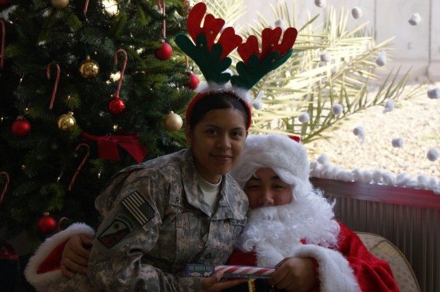 Pfc. Esmeralda Ramirez, a 264th Combat Sustainment Support Battalion radio operator, poses for a photo with Santa.