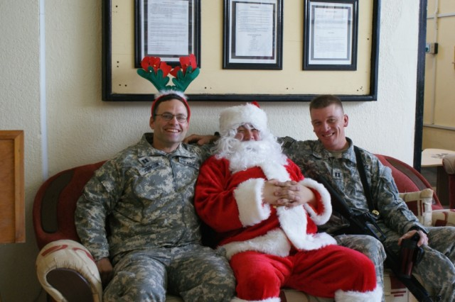 Capt. Myron Johnson, the 264th Combat Sustainment Support Battalion chaplain, Pvt. Edward Shaw, dressed up as Santa, and Capt. Gregory Wilson, the executive officer for 2025th Transportation Company.