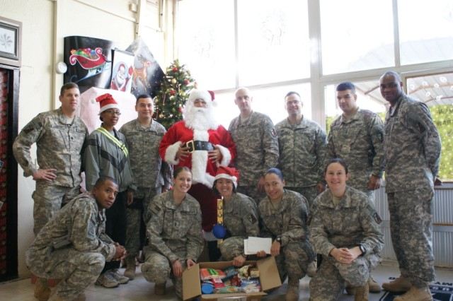 The battalion staff takes a group photo with Santa. Top row from left to right: Lt. Col. Steven Debusk, Sgt. Brittany Brim, 1st Lt. Genaro Morones, Pvt. Edward Shaw, Maj. John Kredo, Capt. Myron Johnson, 1st Lt. Vladimir Carrillo, and Capt. John Twitty. Bottom row from left to right: Capt. Barry White, 1st Lt. Maria Schmitz, Staff Sgt. Carrie Gomez, Capt. Darsharee Saik, and Maj. Sherri Shadrock.