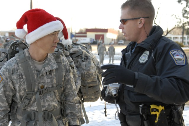 "COLORADO SPRINGS, Colo. - Chaplain Maj. Charlie Lee, 1st Brigade Combat Team, 4th Infantry Division, discusses the foot march route with Colorado Springs Police Department officer, Brett Iverson, Dec. 18. Lee organized the 1st BCT ""Operation: Happy Christmas"" event employing nearly 300 Soldiers of the ""Raider"" Brigade in a foot march to deliver food, clothing and supplies to Colorado Springs' homeless."