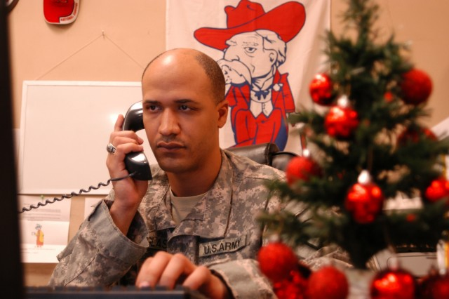 CONTINGENCY OPERATING LOCATION Q-WEST, Iraq - Staff Sgt. Anthony Douglass, a native of Cockrum, Miss., works as the non-commissioned officer in charge of the Mayor Cell Help Desk at Contingency Operating Location Q-West, seen here Dec. 5. He said he received the little Christmas tree from his grandmother.