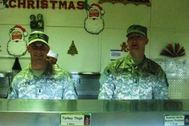 CONTINGENCY OPERATING LOCATION Q-WEST, Iraq - 1st Lt. Brannon M. Poland (left), a platoon leader from Bateville, Miss., and 1st Lt. Robert V. Clark, a platoon leader from Hernando, Miss., serve lunch in the main dining facility at Contingency Operating Location Q-West, Dec. 25. Poland belongs to A Company, 2nd Battalion, 198th Combined Arms, out of Hernando, Miss, and Clark serves with B Company, 2/198th CAB, out of Greenwood, Miss. They participated in a long-standing tradition of leaders serving chow during holiday meals.