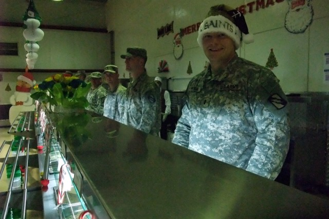 CONTINGENCY OPERATING LOCATION Q-WEST, Iraq - 1st Lt. Jeffrey T. Watkins, a platoon leader from Lafayette, La., wears a New Orleans Saints Christmas hat while serving lunch in the main dining facility at Contingency Operating Location Q-West, Dec. 25. Watkins belongs to A Company, 2nd Battalion, 198th Combined Arms, out of Hernando, Miss. He participated in a long-standing tradition of leaders serving chow during holiday meals.