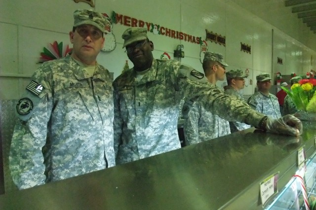 CONTINGENCY OPERATING LOCATION Q-WEST, Iraq - 1st Sgt. John A. Moyer (left), a native of , Senatobia, Miss., and 1st Lt. Jesse L. Hill, executive officer from Meridian, Miss., serve Christmas lunch in the main dining facility at Contingency Operating Location Q-West, Dec. 25. Both belong to C Company, 2nd Battalion, 198th Combined Arms, out of Oxford, Miss. They participated in a long-standing tradition of senior leadership serving chow during holiday meals.