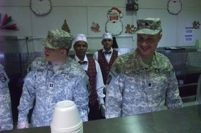 CONTINGENCY OPERATING LOCATION Q-WEST, Iraq - Capt. John Moore (left), of Calendoia, Miss., and Lt. Col. William B. Smith, Jr., of Hattiesburg, Miss., serve Christmas lunch in the main dining facility at Contingency Operating Location Q-West, Dec. 25. Moore is the officer in charge of badging at Q-West, and Smith is the mayor of Q-West. Both belong to Headquarters, Headquarters Company, 2nd Battalion, 198th Combined Arms, out of Senatobia, Miss. They participated in a long-standing tradition of senior leadership serving chow during holiday meals.