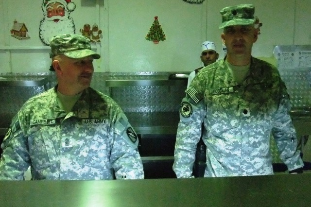 CONTINGENCY OPERATING LOCATION Q-WEST, Iraq - Capt. John Satterfield (left), native of Midway, Ga., and Lt. Col. Kerry Goodman, a resident of Meridian, Miss., serve Christmas lunch in the main dining facility at Contingency Operating Location Q-West, Dec. 25. Satterfield directs the Q-West Department of Public Works, and Goodman commands 2nd Battalion, 198th Combined Arms, headquartered in Senatobia, Miss. They participated in a long-standing tradition of senior leadership serving chow during holiday meals.