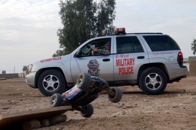 CAR2.JPG CONTINGENCY OPERATING LOCATION Q-WEST, Iraq - Sgt. 1st Class Kenneth E. Guess, a provost marshal from Nettleton, Miss., clocks a toy car speeding 22 miles per hour on Contingency Operating Location Q-West, Dec. 24. Guess issued a warning to Capt. Christopher Wilton, a communications officer from Olive Branch, Miss., that the maximum speed limit was 15 miles per hour. Both Soldiers serve with Headquarters, and Headquarters Company, 2nd Battalion, 198th Combined Arms, out of Senatobia, Miss.,