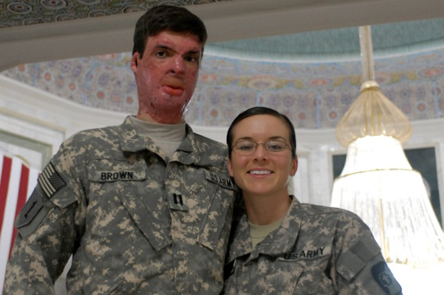Capt. Sam Brown stands with his wife, Capt. Amy Brown, Jan. 1 inside Camp Victory's Al Faw Palace. Brown suffered third degree burns to 30 percent of his body after being struck by an improvised explosive device in Kandahar, Afghanistan, in September 2008.