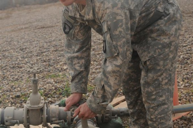 Sgt. Brian Gil, noncommissioned officer in charge of the water site at Contingency Operating Location Poliwoda, Iraq, with the 102nd Quartermaster Company, 80th Ordnance Battalion, 15th Sustainment Brigade, 13th Sustainment Command (Expeditionary), tightens valves leading to the potable water tank Jan. 5 at the COL Poliwoda water site. The water team produces roughly 15,000 gallons of water a day to supply running water for the roughly 500 occupants assigned to the base.