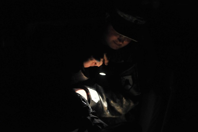 Spc. Shane P. Spieker, West Fargo, N.D., checks his gear before an early morning patrol on Bilince/Billince, Kosovo.