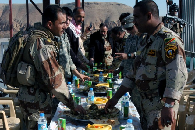 CONTINGENCY OPERATING LOCATION Q-WEST, Iraq - Mississippi Guardsmen share a feast of curried rice and lamb with senior leaders of the Iraqi Army's 26th Brigade on the lift station dock of the Al Qayyarah pump house, Dec. 29. The Mississippians serve with A Company, 2nd Battalion, 198th Combined Arms, 155th Brigade Combat Team, out of Hernando, Miss., the force protection element for Contingency Operating Location Q-West providing security for all missions to the pump house, which supplies potable water to the base. Pictured at the head table wearing a black leather jacket is Col. Hussein Abbas, commander of the 26th Brigade.