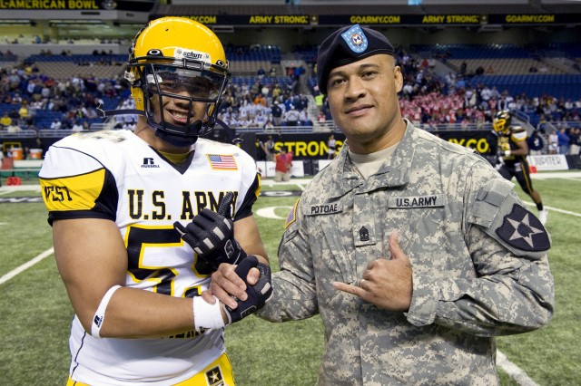 Soldier-Hero 1st Sgt. Aleki Potoae greets his son, Sione, before the start of the Army-sponsored high school all-star game in San Antonio, Texas. Sione is a member of the West team.
