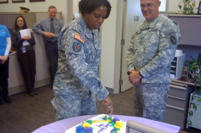 Col. Tracey Nicholson cuts her farewell cake as Maj. Gen. Karl Horst and other staff members look on.
