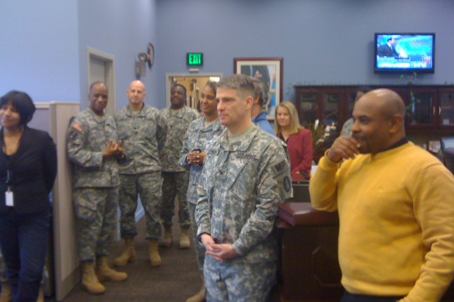 Members of the staff listen as Col. Tracey Nicholson expresses her thanks.