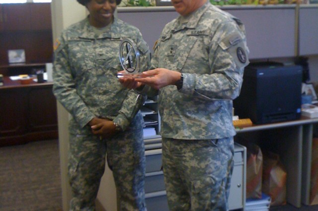 Col. Tracey Nicholson, outgoing Chief of Staff, is presented with a thank you gift by Maj. Gen. Karl R. Horst, Commander of Joint Force Headquarters and the U.S. Army Military of Washington. Col. Nicholson will become the Executive Officer for the Assistant Secretary of the Army for Installations and Environment in the Pentagon.