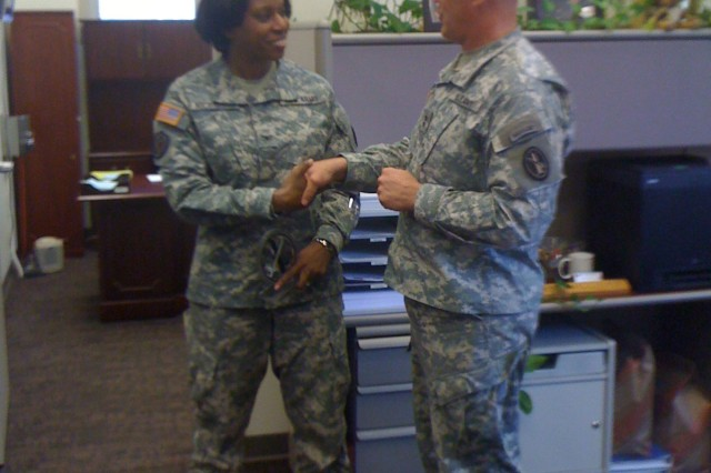 Maj. Gen. Karl R. Horst, presents Col. Tracey Nicholson with a commander's coin.