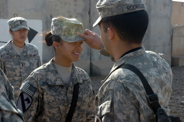 CAMP TAJI, Iraq -  Pfc. Harmony Rodriguez (left), from Victoria, Texas, a cook in Company E, 4th Battalion, 227th Aviation Regiment, 1st Air Cavalry Brigade, 1st Cavalry Division, smiles as her brother, Spc. Jeremiah Rodriguez pins private first class rank  on her patrol cap during a promotion ceremony at 4-227th headquarters Jan. 4. Jeremiah, from Lubbock, Texas, is an aircraft electrician in Company B, 615th Aviation Support Battalion, 1st ACB, and serves on the same camp as his sister.