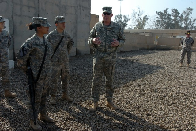 CAMP TAJI, Iraq -  Pfc. Harmony Rodriguez (from left), from Victoria, Texas, a cook in Company E, 4th Battalion, 227th Aviation Regiment, 1st Air Cavalry Brigade, 1st Cavalry Division, and her brother, Spc. Jeremiah Rodriguez, an aircraft electrician from Lubbock, Texas, in Company B, 615th Aviation Support Brigade, 1st ACB, look on as Lt. Col. Randall Haws, 4-227th commander from Vernal, Utah, talks to a formation about Harmony's accomplishments following a promotion ceremony at the 4-227th headquarters Jan. 4.
