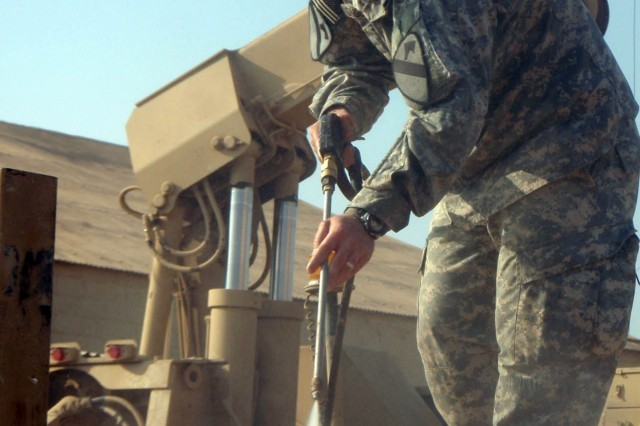 CAMP TAJI, Iraq - Brazoria, Texas native Spc. William Singletary, a welder assigned to Company B, 115th Brigade Support Battalion, 1st Brigade Combat Team, 1st Cavalry Division, uses a pressure washer to clean the flatbed of a palletized load system vehicle on Camp Taji Jan. 5.