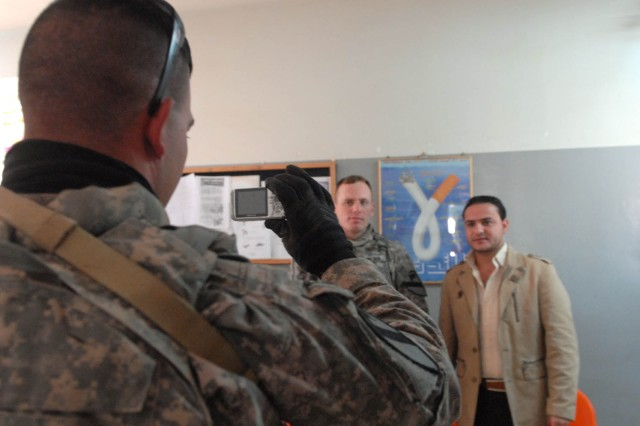 JSS ISTIQLAAL, Iraq - Birmingham, Ala. native, Sgt. Charles Ray (left), an intelligence support team representative for Troop A, 1st Squadron, 7th Cavalry Regiment, 1st Brigade Combat Team, 1st Cavalry Division, photographs the head doctor at a local hospital for their records at Joint Security Station Istiqlaal Dec. 10. 1st Sqdn., 7th Cav. Regt., Soldiers are gathering and compiling vital information about their area of operations to pass to the incoming unit.