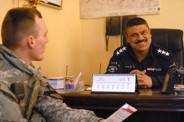 JSS ISTIQLAAL, Iraq - Huntsville, Ala. native, 2nd Lt. John Wilson (left), a platoon leader assigned to 1st Squadron, 7th Cavalry Regiment, 1st Brigade Combat Team, 1st Cavalry Division, visits the commander of a local federal police unit to gather some missing information for the units' continuity book at Joint Security Station Istiqlaal Dec. 12. The 1st Sqdn., 7th Cav. Regt., Soldiers are compiling missing information to pass on to the incoming unit.