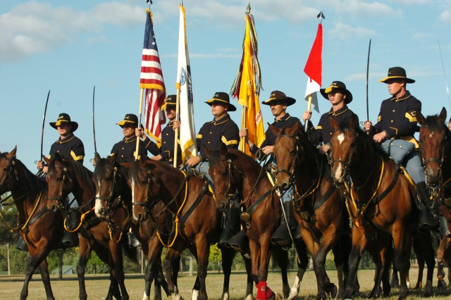 FORT ROBINSON STATE PARK, Neb. - The Fort Carson Mounted Color Guard bears the National Colors, marching in formation at the forefront of members of the National Cavalry Association, at the Fort Robinson State Park Parade Field. The parade marked the first day of the 2009 National Cavalry Competition, part of the NCA Annual Bivouac, held in Nebraska this year.