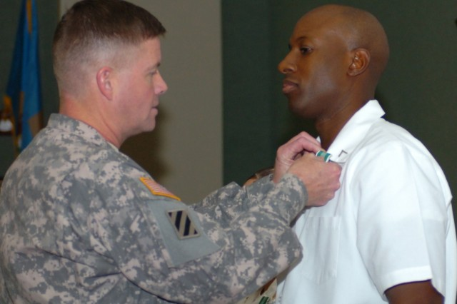 FORT CARSON, Colo. - Maj. Gen. David G. Perkins, commanding general, 4th Infantry Division and Fort Carson, awards an Army Commendation Medal to Pvt. Kenyon Knox, a food service specialist assigned to the Forward Support Company, 1st Battalion, 8th Infantry Regiment, 3rd Brigade Combat Team, 4th Inf. Div., for taking first place at the annual Mountain Post military cooking competition and becoming the Fort Carson Junior Chef of the Year. Perkins and Command Sgt. Maj. Daniel A. Dailey presented installation awards to the Mountain Post's best Soldiers and Department of Defense civilians during the 4th Inf. Div. and Fort Carson 4th Quarter, Fiscal Year 2009 Installation Awards Ceremony Oct. 23 at the division headquarters.