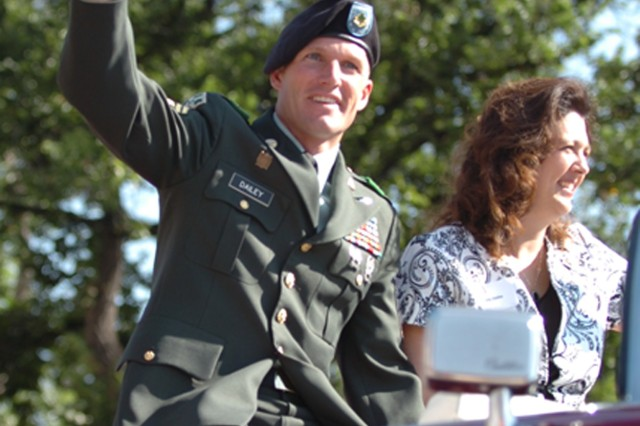"""COLORADO SPRINGS, Colo. - Sgt. Maj. Daniel Dailey, senior enlisted leader of the 4th Infantry Division, and wife, Holly, wave to spectators Aug. 29 during the Red, White and Brave Parade in downtown Colorado Springs. Dailey said that the local community of Colorado Springs and the greater Colorado area are doing an outstanding job of supporting Fort Carson Soldiers. More than 40,000 citizens attended the event organized by local community leaders to honor the Soldiers, who have served in Iraq and Afghanistan and welcome the """"Ivy"""" Division back to Colorado."""