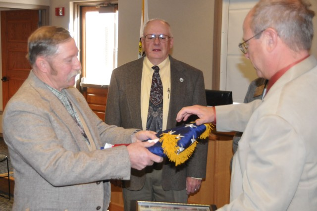 CRIPPLE CREEK, Colo. - Mr. Edward Keeser, tactical safety specialist of 2nd Brigade Combat Team, 4th Infantry Division, presents Jim Ignatius, chairman of Teller County Board of County Commissioners, with the National Colors Nov. 25. Keeser flew the flag in Iraq during the 2nd BCT, 4th Inf. Div.'s year-long deployment to Iraq. Keeser gave the flag to Teller County as a gift for the local community's support of the troops.