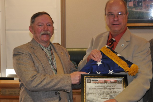 CRIPPLE CREEK, Colo. - Edward Keeser, left, tactical safety specialist of the 2nd Brigade Combat Team, 4th Infantry Division, and Jim Ignatius, chairman of Teller County Board of County Commissioners, pose with the National Colors and Certificate of Authenticity presented to Teller County Nov. 25. The brigade flew the colors in Iraq, during the brigade's recent yearlong deployment, and presented it to the county officials to show appreciation for the local community's support of the troops.
