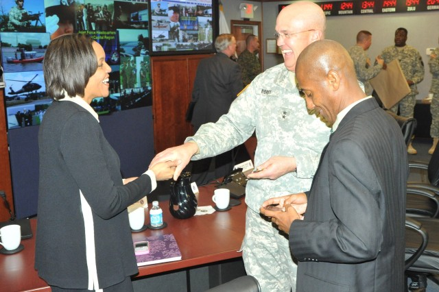 Maj. Gen. Karl R. Horst (center) presents a commander's coin to Millicent Williams (left) director of the District of Columbia Homeland Security and Emergency Management Agency (DCHSEMA) and Neil Albert, District of Columbia city administrator.
