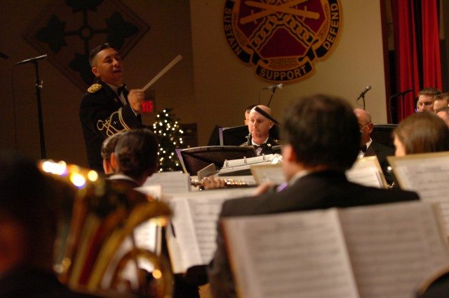 FORT CARSON, Colo. - Chief Warrant Officer 2 Marvin Cardo, commander and conductor of the Ivy Division Band, leads the Fort Carson Holiday Concert, playing classical and contemporary musical arrangements for the Fort Carson and greater Colorado Springs communities at McMahon Auditorium Dec. 4. The Ivy Division Band performed traditional and contemporary holiday classics during a free concert showcasing musical arrangements and vocal performances celebrating the Christmas spirit.