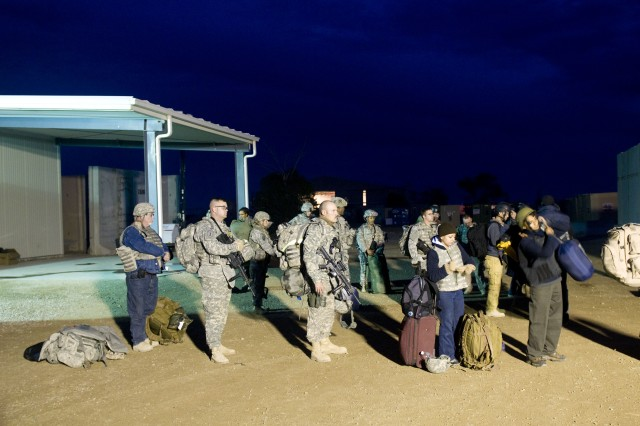 Service members and civilians wait to board their flight outside the new passenger terminal at Contingency Operating Location Speicher, Iraq.