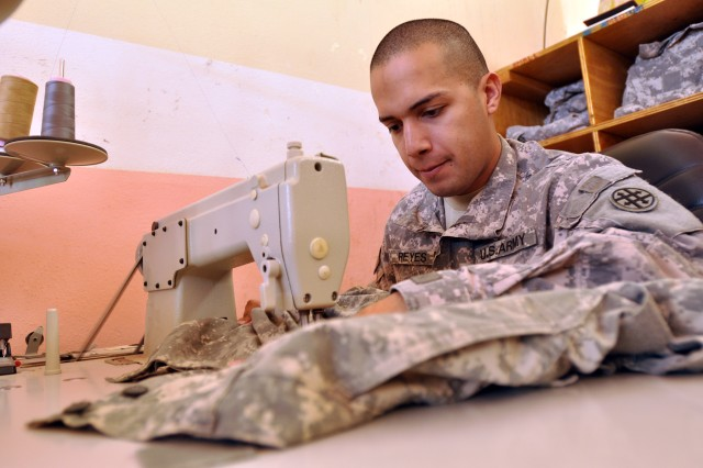 Spc. Agapito Reyes, a 263rd Quartermaster Company shower, laundry, and clothing repair specialist and Sanelizario, Texas, native, repairs a uniform here Jan. 8. (U.S. Army photo by Sgt. Matthew C. Cooley, 15th Sustainment Brigade public affairs)