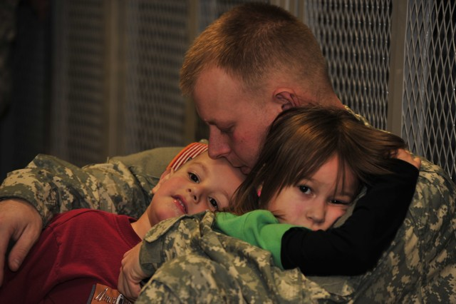 Pfc. Chris Paterson, a native of Hudson, Ohio, holds his daughter Aliva and son Foster before deploying to Afghanistan from Fort Drum, N.Y., Jan. 9. Paterson is an infantryman assigned to Charlie Company, 2nd Battalion, 22nd Infantry Regiment, which is part of the 10th Mountain Division's 1st Brigade Combat Team. His battalion is the first of six from the brigade that are deploying with the troop surge in support of Operation Enduring Freedom.