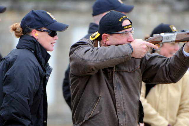U.S. Army Marksmanship Unit's Sgt. 1st Class Joetta Dement has a shooter's eye on San Antonio Stock Show and Rodeo Assistant President for Volunteers Mark Colaw while he shoots skeet Jan. 7 at the San Antonio Gun Club. USAMU Soldiers from Fort Benning, Ga., gave a trick shooting demonstration and provided instruction as a prelude to the 10th annual U.S. Army All-American Bowl played Jan. 9 at the Alamodome.