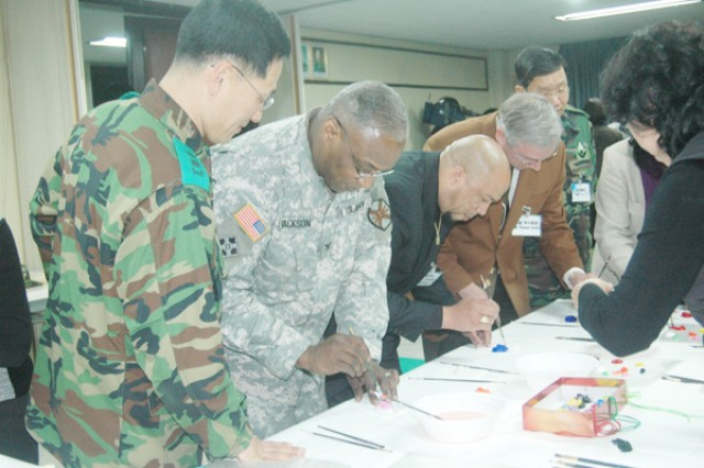 Col. Larry 'Pepper' Jackson (second from left), USAG-Red Cloud commander, Eliott Bradley (second from right), USAG-RC director of Emergency Services Richard Davis (right), USAG-RC deputy commander, paint miniature masks during their visit to the 65th Republic of Korea army. The USAG-RC and Casey command group, and the  directors and special staff paid a visit Jan. 6 to the 65th Republic of Korea army camp for their annual community relations Good Neighbor program. After the briefings, video presentations and entertainment by Korean singers, fan dancers and musicians, everyone was given an opportunity to paint masks, practice calligraphy and practice playing  Korean drums.