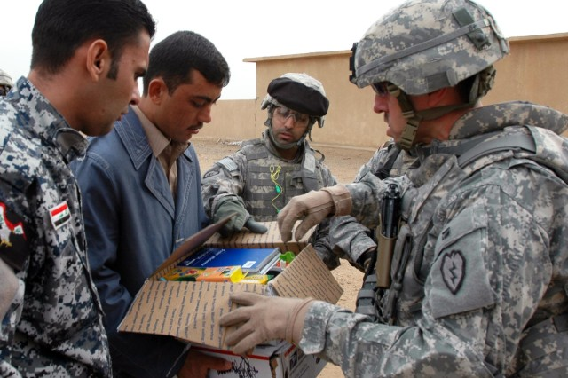Command Sgt. Maj. Jesus Ruiz (right), command sergeant major, 25th Combat Aviation Brigade, Task Force Wings, gives a box of school supplies to the son of a local muhktar in al Warda, near Tikrit, Iraq, Dec 30. Command Sgt. Maj. Ruiz and the Quick Reaction Force team from Company A, 209th Aviation Support Battalion, TF Lobos, visited local schools and other villages in the surrounding areas near Contingency Operating Base Speicher. (Photo by: Sgt. 1st Class Tyrone C. Marshall Jr.  25th Combat Aviation Brigade Public Affairs)