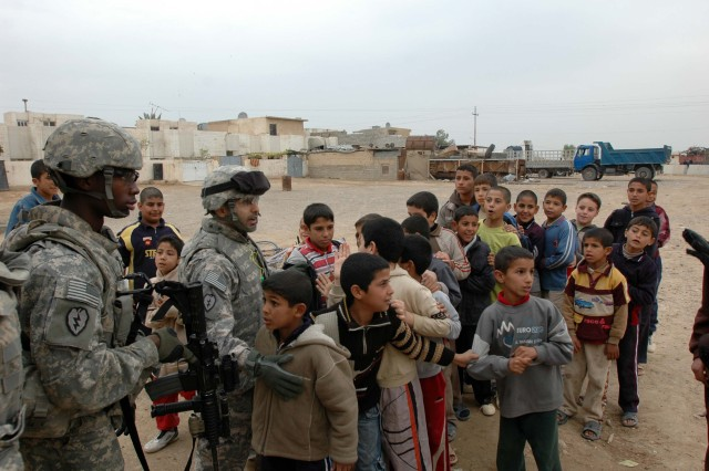 Specialist Rico White (left), a member of the Quick Reaction Force (QRF), Company A, 209th Aviation Support Battalion, Task Force Lobos, and Mike, an interpreter, greet children and line them up to hand out candy in a small village near Tikrit, Iraq, Dec. 30. The QRF, based at Contingency Operating Base Speicher, conducted a site visit for local Iraqi schools as polling sites.   (Photo by: Sgt. 1st Class Tyrone C. Marshall Jr.  25th Combat Aviation Brigade Public Affairs)