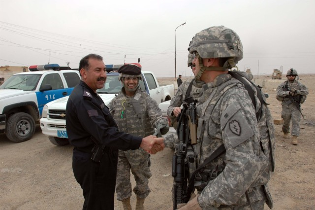 Command Sgt. Maj. Jesus Ruiz (right), command sergeant major, 25th Combat Aviation Brigade, Task Force Wings, accompanied by members of the Quick Reaction Force team, Company A, 209th Aviation Support Battalion, Task Force Lobos, greet Lt. Col. Ghazi Hamed Goma'a, Iraqi police chief for al Aswar, in al Sequora, Iraq, Dec. 30.  The group visited local Iraqi schools and villages near Contingency Operating Base Speicher.  (Photo by: Sgt. 1st Class Tyrone C. Marshall Jr.  25th Combat Aviation Brigade Public Affairs)
