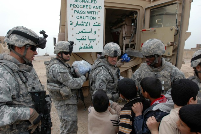 Command Sgt. Maj. Jesus Ruiz (center), command sergeant major, 25th Combat Aviation Brigade, Task Force Wings, passes out candy and small gifts to children in the al Sequora area, near Tikrit, Iraq, Dec 30. Command Sgt. Maj. Osvaldo Martell (far left), command sergeant major, 209th Aviation Support Battalion, TF Lobos, and his Quick Reaction Force team also visited local schools and villages in the surrounding areas near Contingency Operating Base Speicher. (Photo by: Sgt. 1st Class Tyrone C. Marshall Jr.  25th Combat Aviation Brigade Public Affairs)
