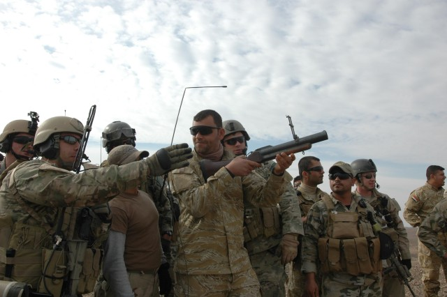 A 12th Iraqi Army Special Operations Company Soldier listen to instructions from an Operational Detachment-Alpha 1216 team member before marking an area with a 40-mm round from a M-74 grenade launcher before a call for fire near Hawijah, Iraq, Dec. 26 The 12th IA SOC and ODA 1216 conduct joint missions to provide security and stability operations in Kirkuk Province. (Photo by:  Sgt. 1st Class Tyrone C. Marshall  25th Combat Aviation Brigade Public Affairs)